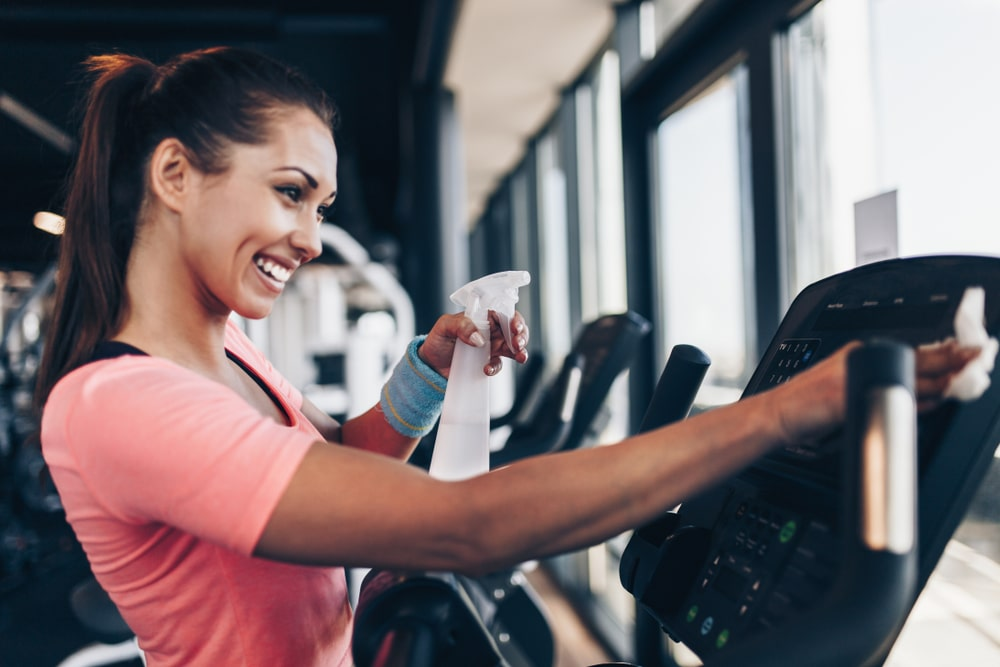 woman cleaning gym machine