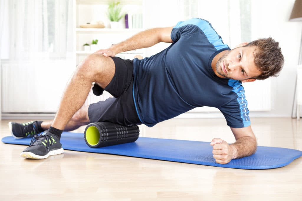 Man exercising with a foam roll