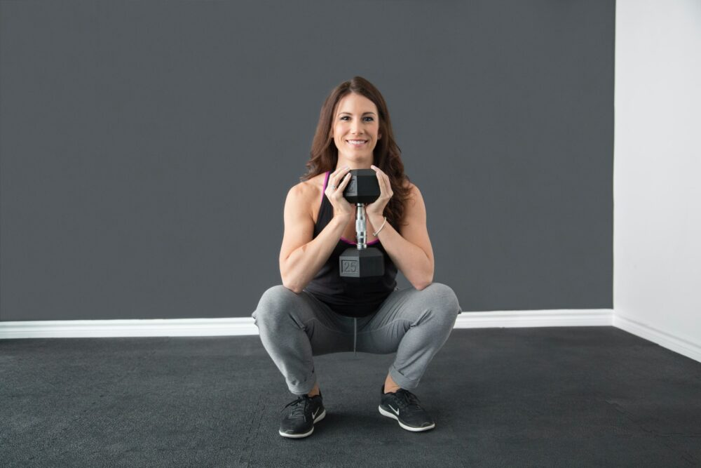 woman doing squats with a dumbell